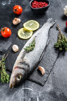 Fresh sea bass fish with herbs and lemon on a black plate.