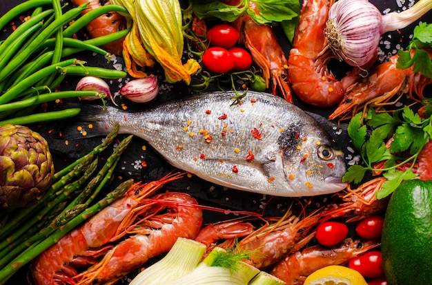 Fresh sea bream or dorado fish and prawns with ingredients and vegetables for cooking