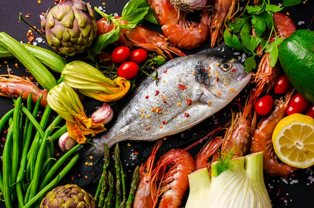 Fresh sea bream or dorado fish and prawns with ingredients and vegetables for cooking.