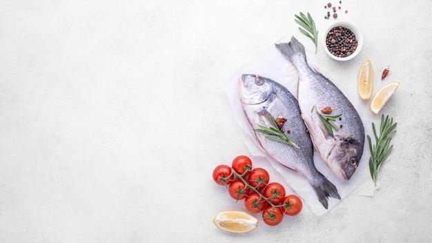 Свежая рыба морского леща с зеленью и помидорами