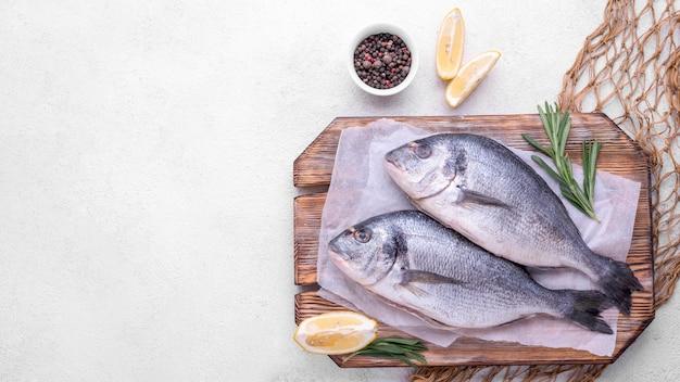 Fresh sea bream fish on wooden board copy space