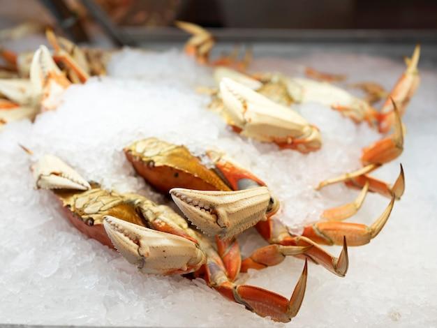 魚市場で販売するための氷で新鮮な海のカニのカバー