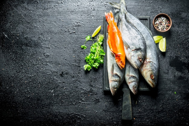 Fresh sea fish with lime slices, parsley and spices. on black rustic background