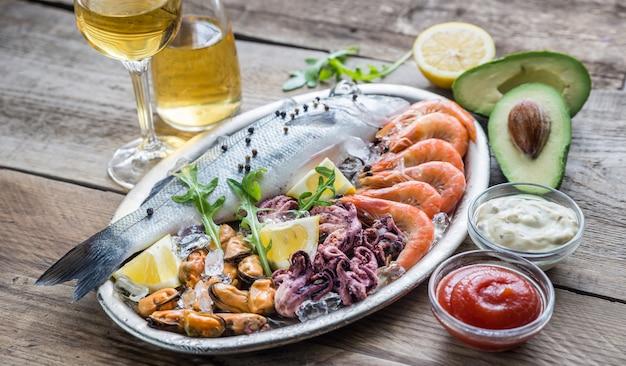 Свежий сибас с морепродуктами на подносе