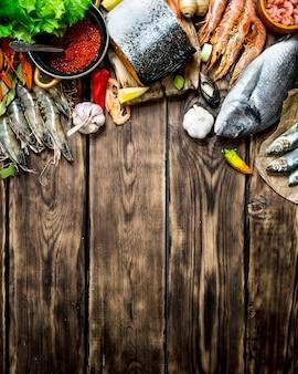 新鮮なシーフード。エビ、甲殻類、その他の海洋生物からのさまざまなシーフード。木製の背景に。