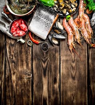 Свежие морепродукты. разнообразные морепродукты из креветок, моллюсков и других морских обитателей. на деревянном столе.