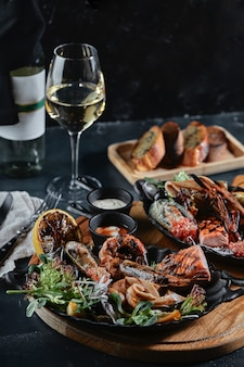 돌 테이블에 신선한 해산물과 화이트 와인. 요리사가 제공하는 굴, 새우, 가리비, 오징어는 접시에 아름답게 깔려 있고 어두운 콘크리트 배경입니다.