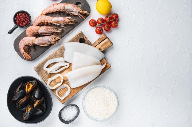 Ассорти из свежих морепродуктов для паэльи на белом текстурированном фоне, плоская планировка с копией пространства