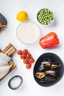 Ассорти из свежих морепродуктов для паэльи на белом текстурированном фоне, плоская планировка