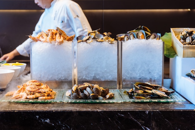 Fresh seafood buffet line including alaska king crab, shrimp, lobster, oyster and perna vi