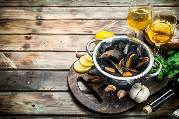 Моллюски из свежих морепродуктов в горшочке с белым вином. на деревянном фоне.
