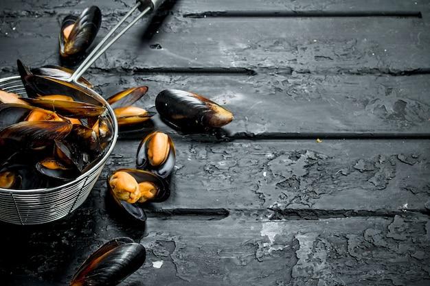Моллюски свежие морепродукты в кастрюле. на черном деревенском.