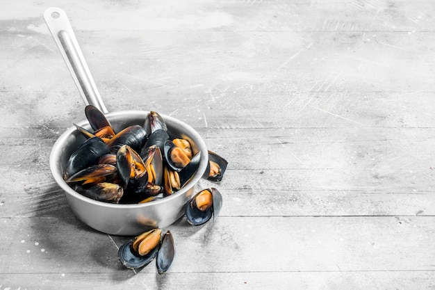 Fresh seafood clams in a saucepan on rustic table.