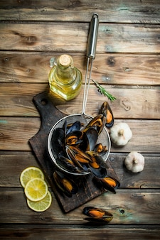 Fresh seafood clams with lemon wedges. on a wooden background.