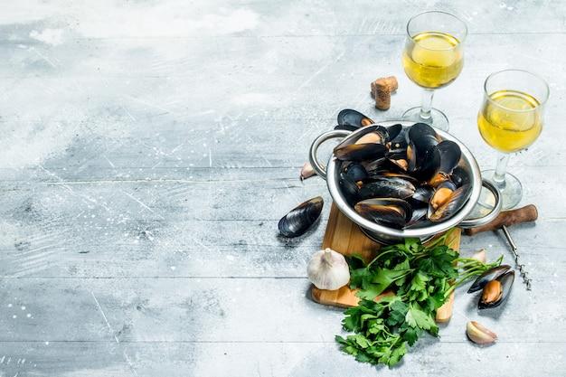 Моллюски из свежих морепродуктов с петрушкой и белым вином. на деревенском фоне.