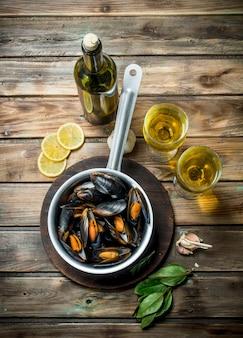 Моллюски из свежих морепродуктов с белым вином. на деревянном.