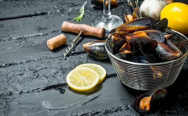 Моллюски из свежих морепродуктов с белым вином. на черном деревенском фоне