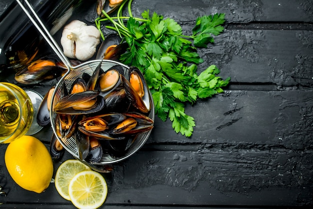 Fresh seafood clams with white wine and parsley. on black rustic background.
