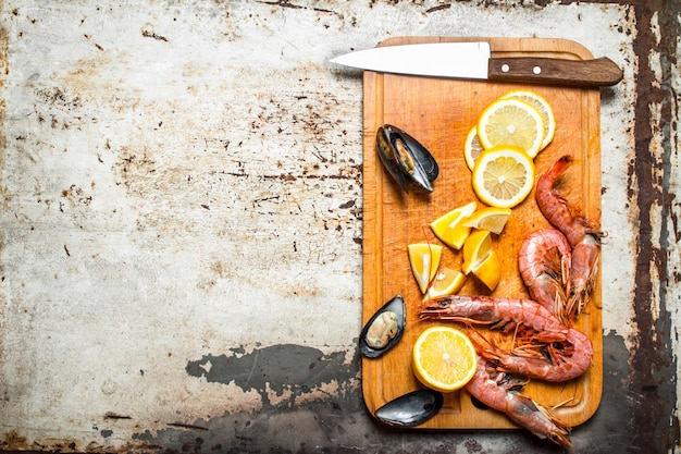 素朴な背景にエビ、貝、レモンと新鮮なシーフードまな板