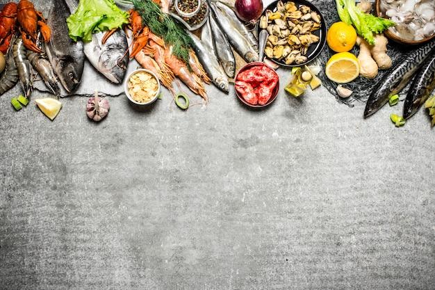 Свежие морепродукты. разные рыбы, креветки и моллюски с ломтиками лимонных специй на бетоне.