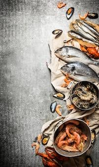 돌 배경에 신선한 해산물 신선한 새우, 생선 및 조개