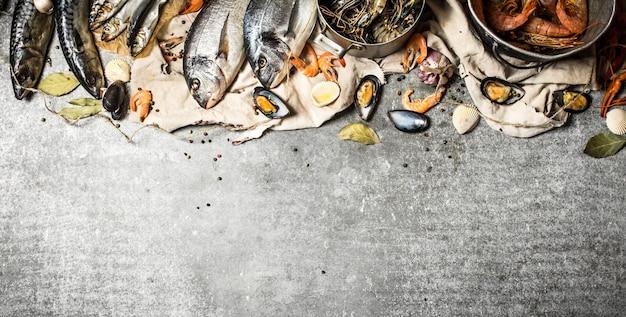 Свежие морепродукты. свежие креветки, рыба и моллюски. на каменном столе.