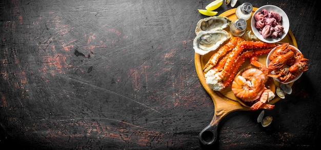 석 회와 향신료와 함께 커팅 보드에 신선한 해산물. 어두운 소박한 배경에