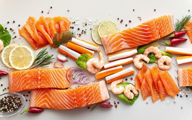 スパイス、野菜、オリーブオイルをテーブルに置いた新鮮な魚介類:スーパーマーケットや魚の寿司レストラン向けの新鮮なスモークサーモン、エビ、カニの棒。
