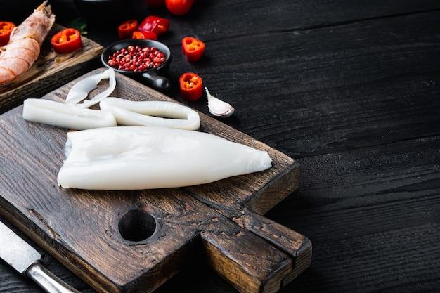 新鮮なシーフード、テキスト、食べ物の写真のためのスペースを持つ黒い木製のテーブルの上に木の板に生イカ。