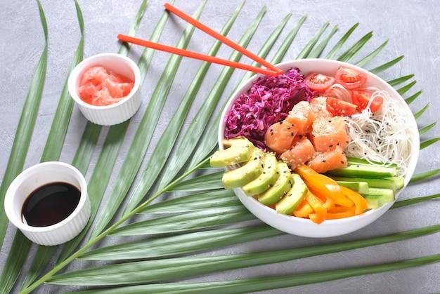 新鮮なシーフードのレシピ。自然食品。クリスタルヌードル、新鮮なキャベツ、アボカド、チェリートマトが入った新鮮なサーモンポークボウル。フードコンセプトポークボウル