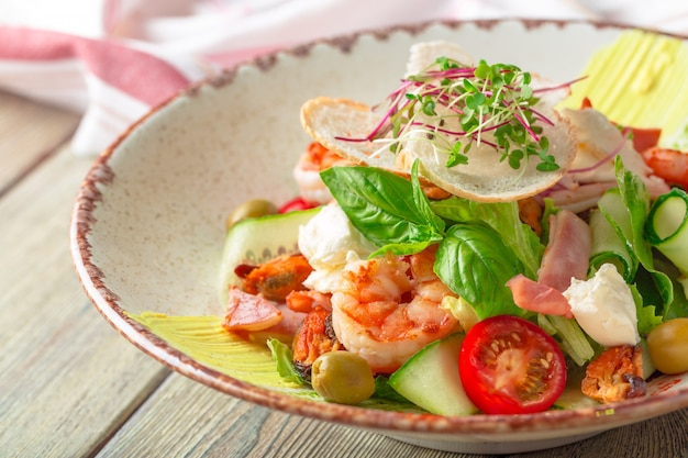 Fresh seafood salad served with prawns and greens