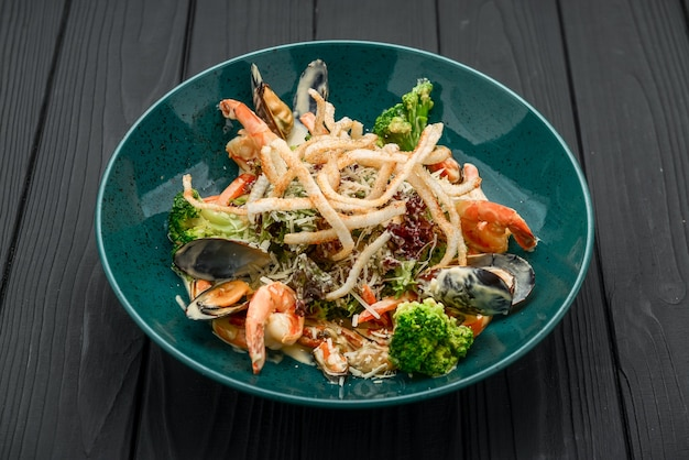Fresh seafood salad with shrimps, mussels and vegetables on a black