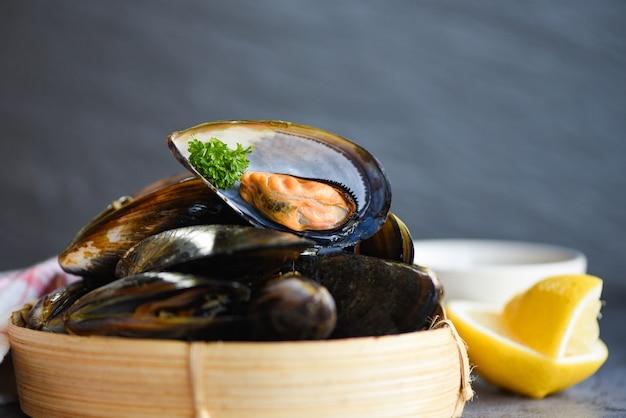 Свежие морепродукты из морепродуктов в ресторане мидии оболочки пищи на бамбука пароход - мидии с травами лимоном на фоне готовить пароход пищи