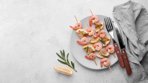 新鮮な魚介類のエビの串焼きとカトラリー