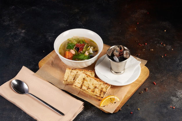 Fresh seafood soup in bowl, dark background