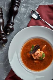 暗い背景、上面図に白いプレートで新鮮なシーフードスープ