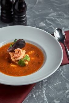 Fresh seafood soup in a white plate on dark background, side view