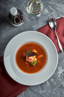 Fresh seafood soup in a white plate on dark background, top view
