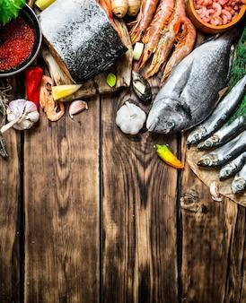 Свежие морепродукты. разнообразие креветок из морепродуктов, рыбы и моллюсков. на деревянном фоне