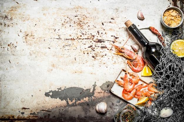 Свежие морепродукты вино с креветками и специями с рыболовной сетью на деревенском фоне