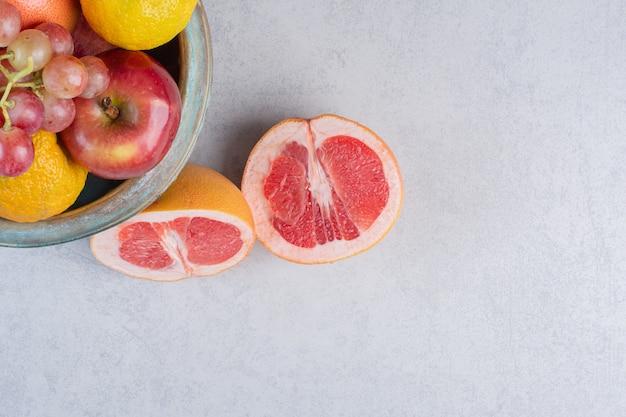 Frutta fresca di stagione mela uva e pompelmo in una ciotola su sfondo grigio.