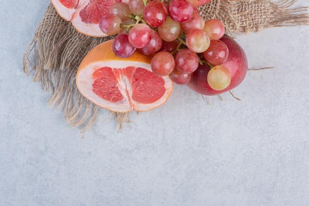 Frutta fresca di stagione mela uva e pompelmo su sfondo grigio.