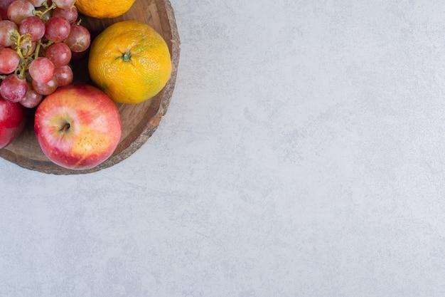 Frutta fresca di stagione mela uva e mandarini su tavola di legno.