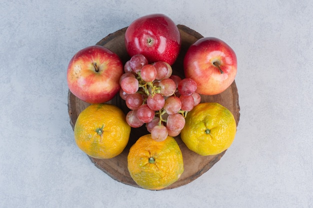 Fresh seasonal fruits. red apple and grape with tangerine.