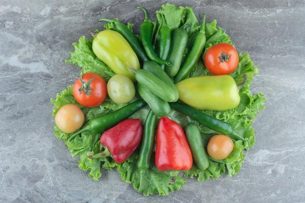 Verdure fresche di stagione su superficie grigia