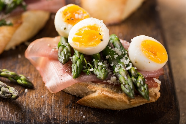 Fresh sendwich with ham, asparagus and quail eggs