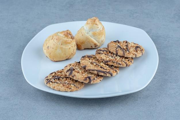 白い皿に新鮮なゴマクッキー。写真をクローズアップ。
