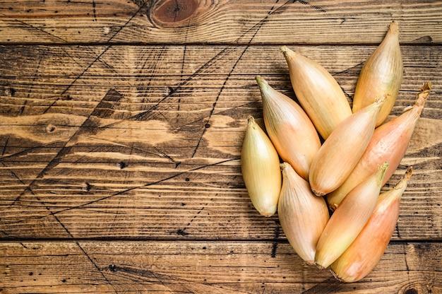 Свежий лук-шалот луковицы на кухонном столе. деревянный фон. вид сверху. скопируйте пространство.