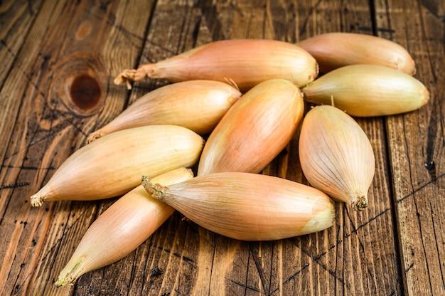 Свежий лук-шалот луковицы на кухонном столе. деревянный фон. вид сверху.