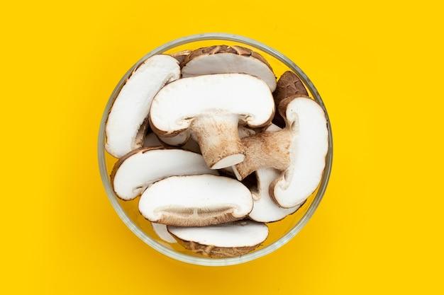 노란색 바탕에 유리 그릇에 신선한 표고 버섯.